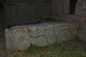 Piece of an ancient stone in which a chariot pulling by a horse is sculpted.